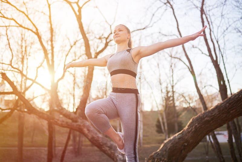 瑜伽席子的女孩在公园 库存照片