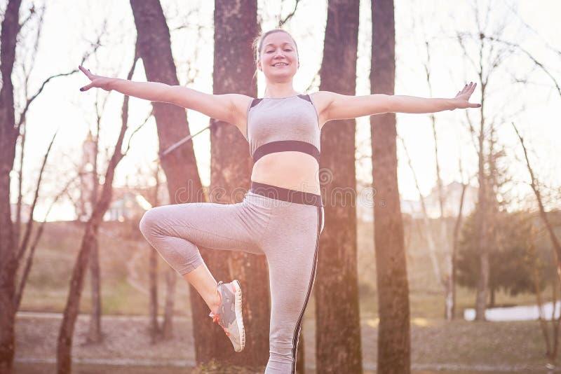 瑜伽席子的女孩在公园 免版税图库摄影