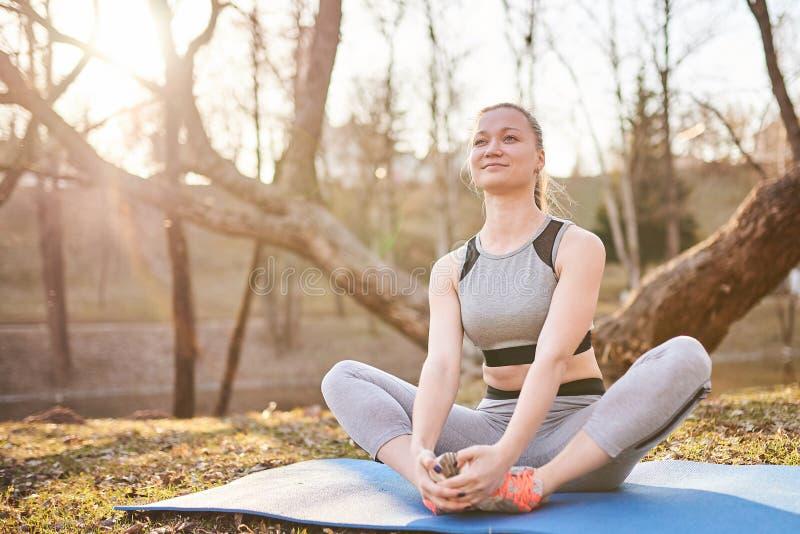 瑜伽席子的女孩在公园 图库摄影