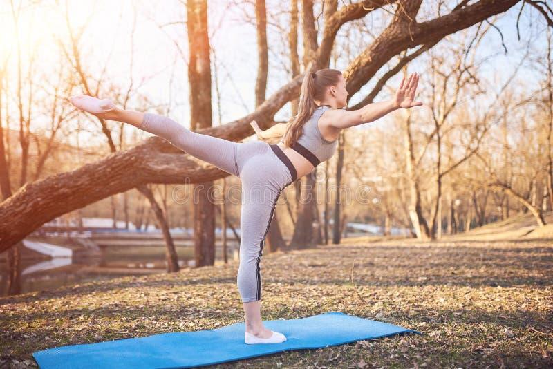 瑜伽席子的女孩在公园 免版税库存图片