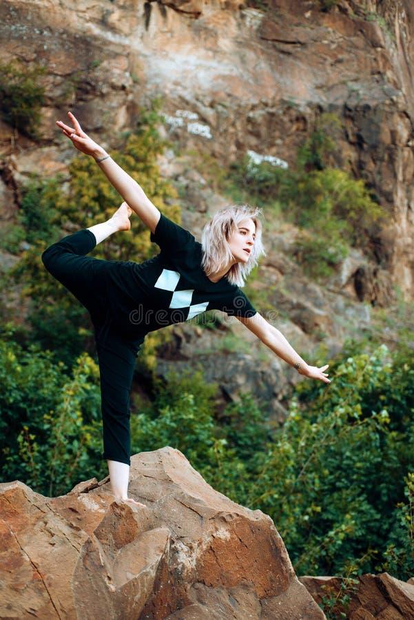 瑜伽帮助发现和谐 妇女灵活的身体实践瑜伽自然背景 舒展身体锻炼的女孩 ?? 图库摄影