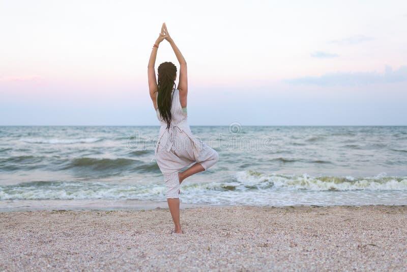 瑜伽思考在海滩日落的凝思妇女放松在瑜伽姿势,树姿势, vrksasana 享受前夕的轻松的平静的妇女 库存图片