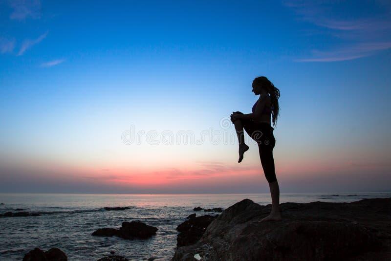 瑜伽或健身在海的妇女剪影在惊人的日落期间.图片