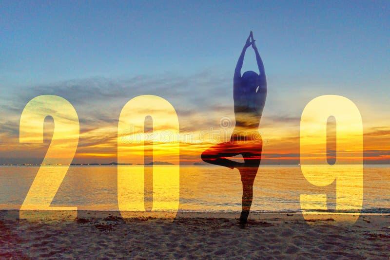 瑜伽新年快乐卡片2019年 作为第2019一部分的剪影生活方式女子实践的瑜伽身分在日落的海滩附近 免版税图库摄影