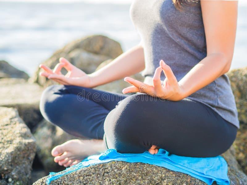 瑜伽概念 在海滩的特写镜头妇女手实践的莲花姿势在日落 免版税库存图片
