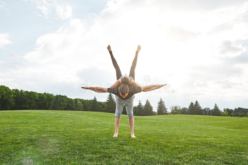瑜伽灵活性 做在一棵草的年轻健康夫妇acro瑜伽在晴朗的早晨 健康生活方式 各种各样的瑜伽 免版税库存图片