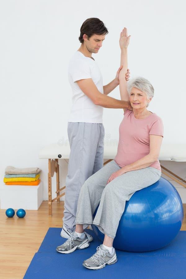 瑜伽球的资深妇女与一位理疗师 免版税库存图片