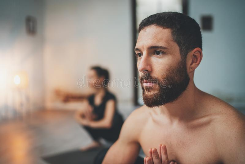 瑜伽练习类概念 年轻女人和人实践的瑜伽户内 做锻炼的两运动的人 免版税库存照片