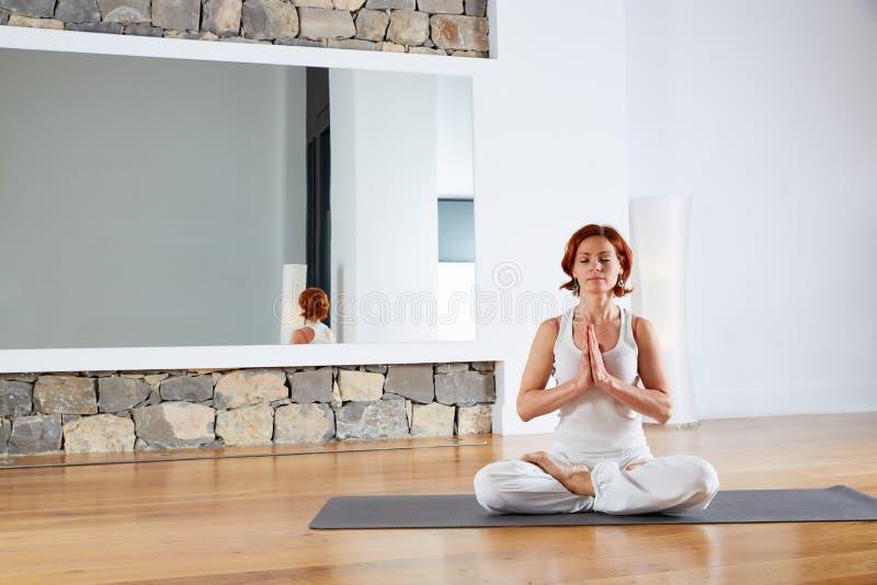 瑜伽莲花在木地板的姿势凝思 免版税库存图片