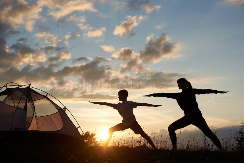 瑜伽行使由家庭夫妇的战士姿势在早晨天空背景的破晓与稀稀落落的云彩和明亮的太阳的 库存图片