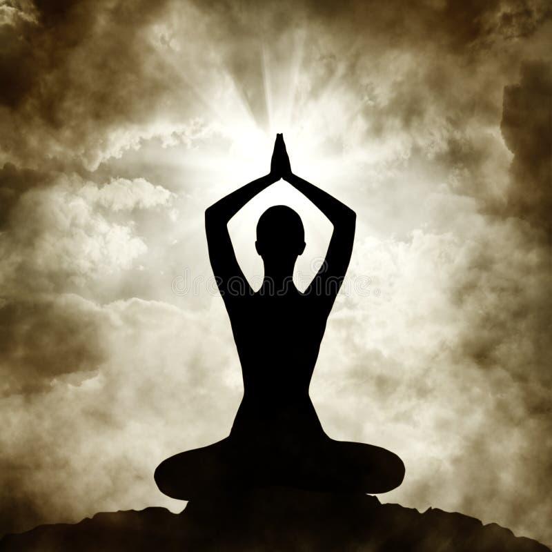 瑜伽身体行使在日落天空背景的姿势剪影 免版税库存图片