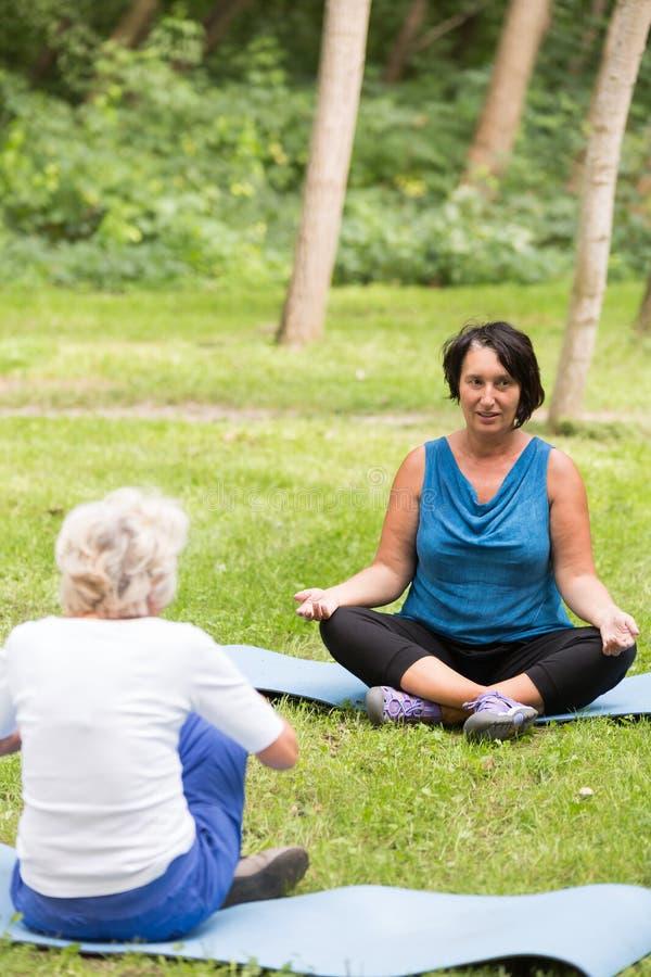 瑜伽辅导员和一名年长妇女 库存照片