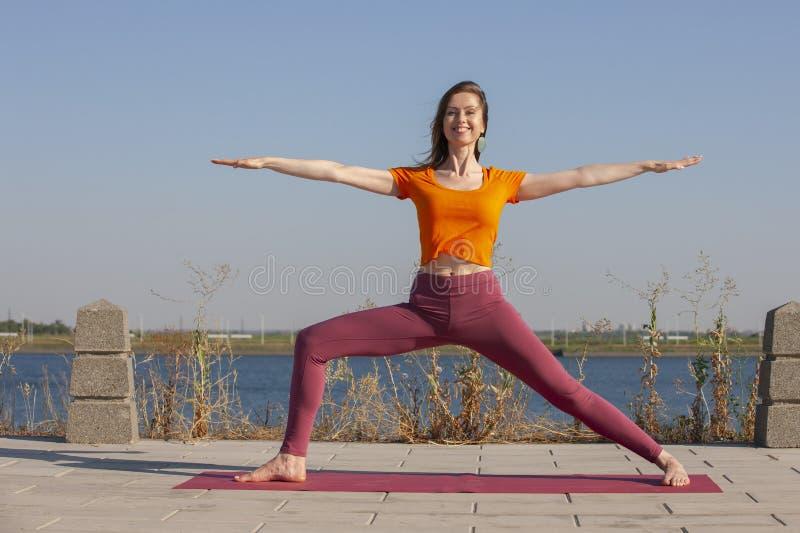 瑜伽锻炼-做瑜伽在公园体育健康概念的妇女姿势凝思 库存照片