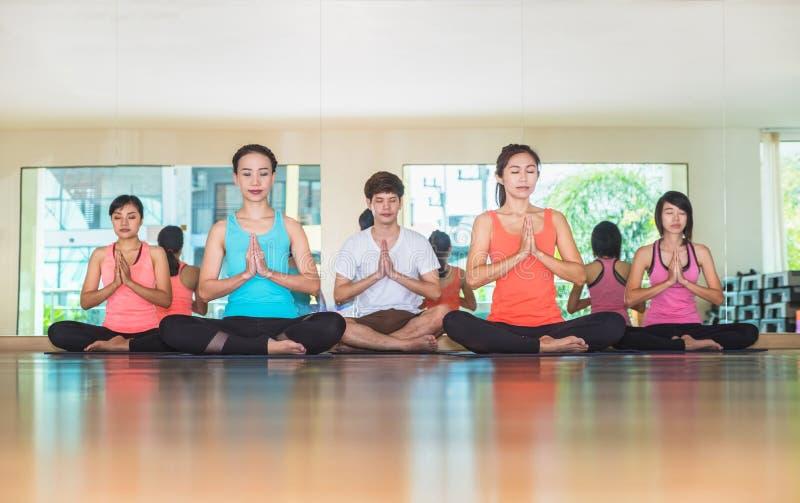 瑜伽类在演播室屋子,做namaste姿势机智的人里 库存图片