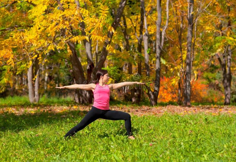 瑜伽virabhadrasana姿势. 公园, 灵活.