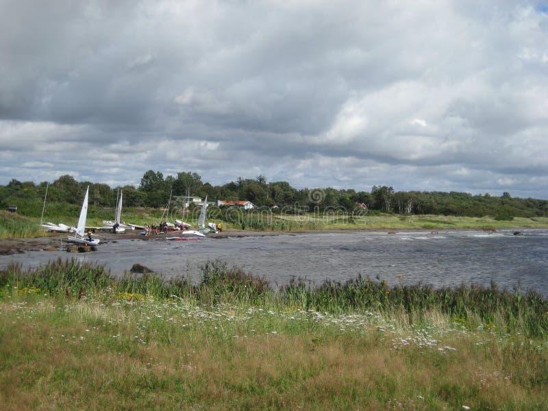 瑞典哈尔姆斯塔德水安置帆船夏天云彩草灰色 库存照片