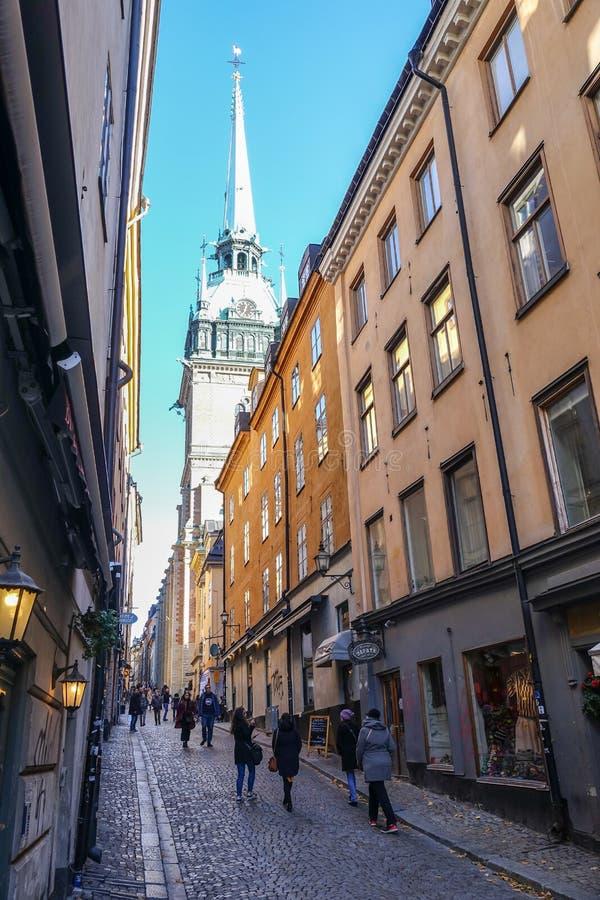 瑞典语的德国教会:Tyska kyrkan在老房子之间的狭窄的胡同在stan的Gamla,斯德哥尔摩,瑞典老镇  库存照片