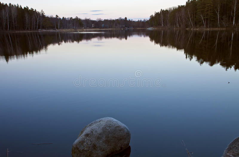 瑞典 黄昏的小湖与树反射 库存图片