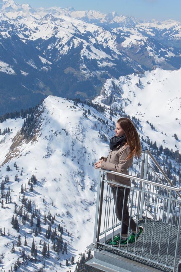 瑞士山中的牧人小屋的大阳台的美丽的棕色毛发的女孩在高山的 一个女孩和一个夏日在山 库存照片