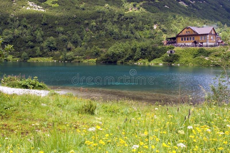 瑞士山中的牧人小屋绿色湖在旁边 免版税库存图片