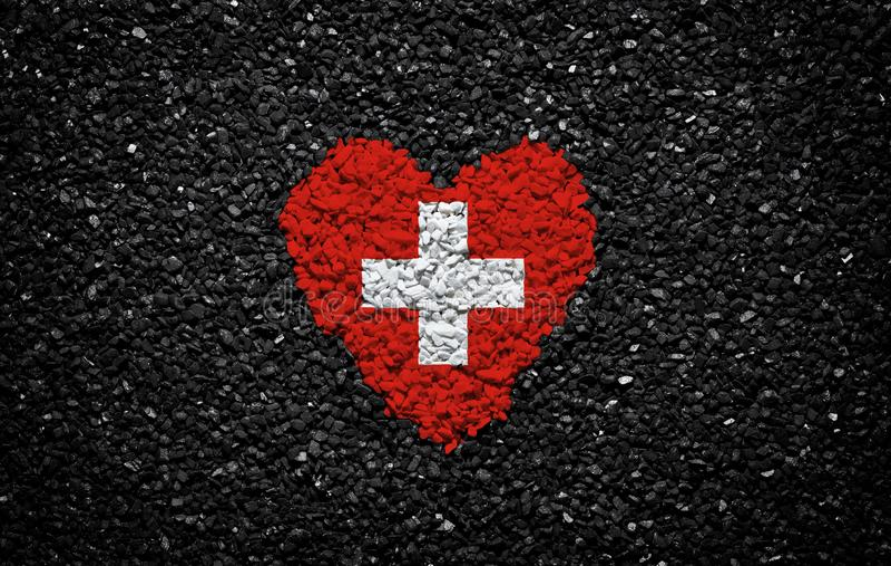 瑞士的旗子,瑞士旗子、心脏在黑背景,石头、石渣和木瓦,织地不很细墙壁 免版税库存照片