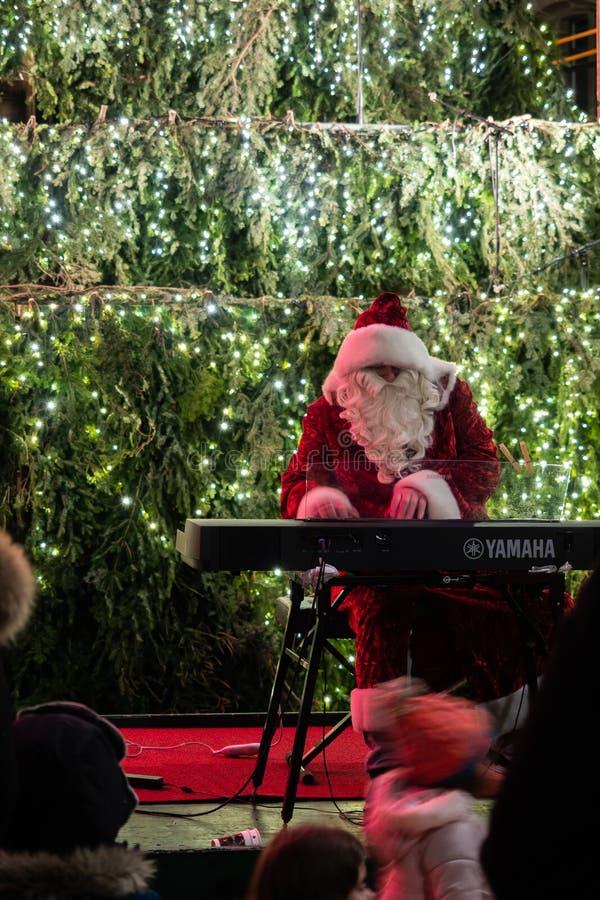 瑞士苏黎士- 2018作为圣诞老人戏剧与一架电子钢琴的圣诞节音乐假装的12月22日A人 免版税库存照片