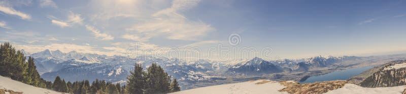 瑞士阿尔卑斯mountai全景视图在与森林和蓝天的冬天 免版税库存图片