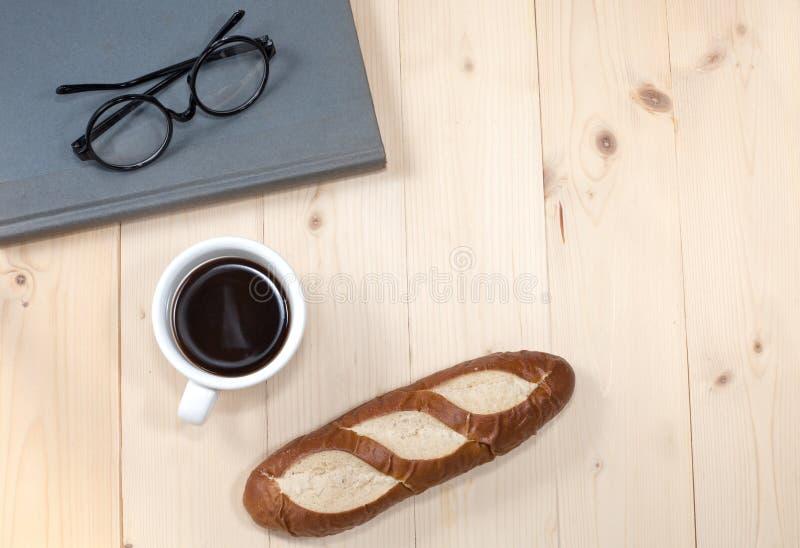 玻璃、书、咖啡和面包反对 免版税库存照片