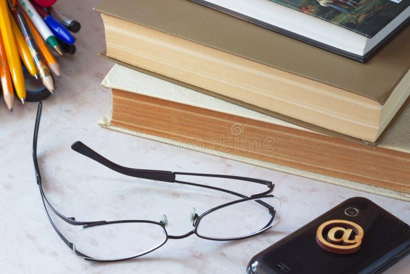 玻璃、手机、旧书和膝上型计算机 免版税库存图片