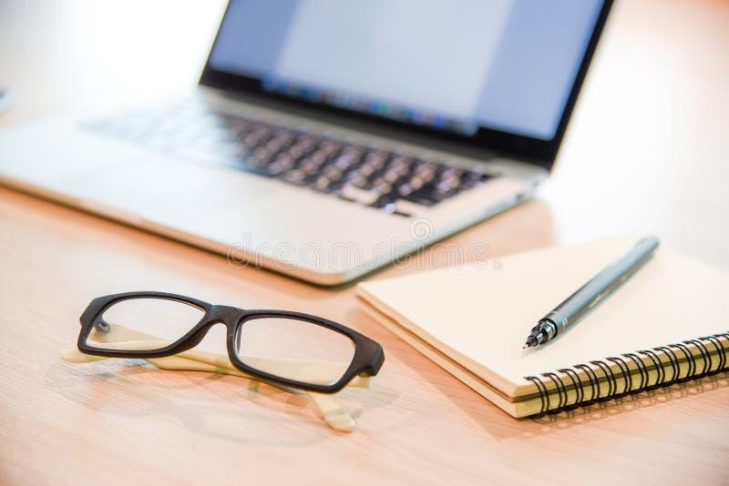 玻璃、笔记本和膝上型计算机在木办公桌上 免版税库存照片
