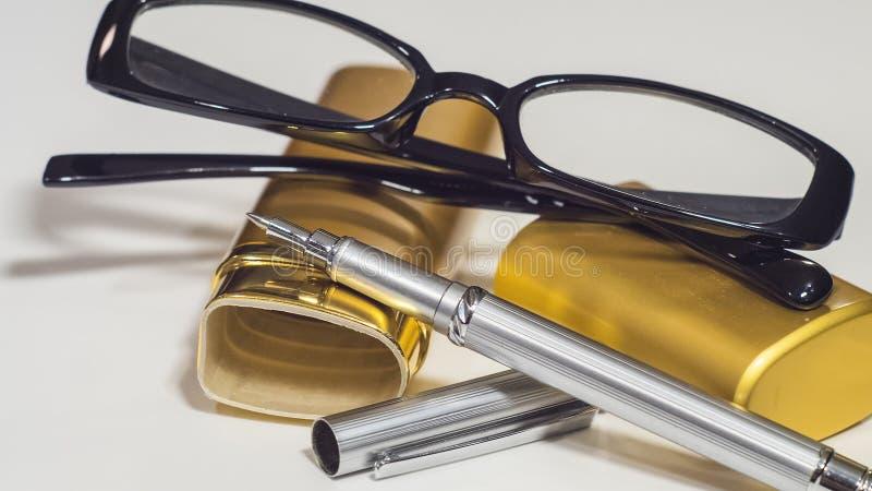 玻璃、金盒和笔 白色孤立背景 特写镜头 免版税库存照片