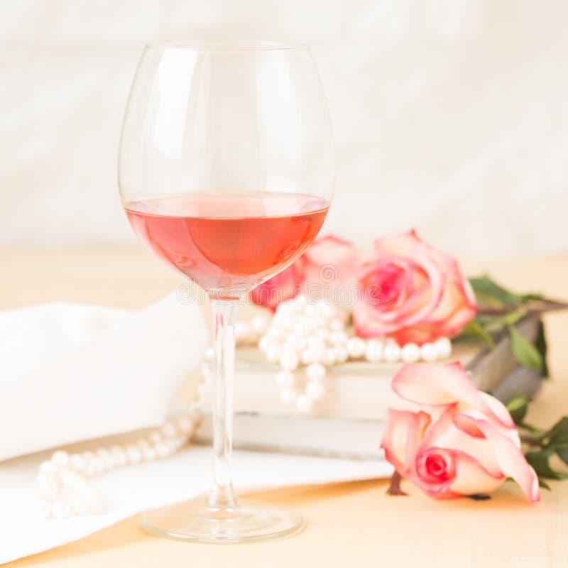 玻璃上升了与葡萄酒书和珍珠 免版税库存图片