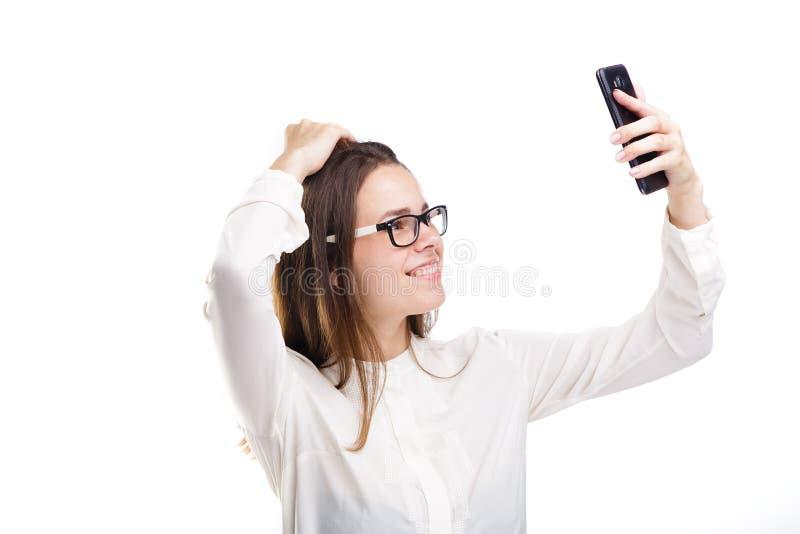 玻璃和一件白色衬衣的美丽的女孩在照相机电话拍照片的她自己,在白色被隔绝的背景的selfie 免版税库存图片