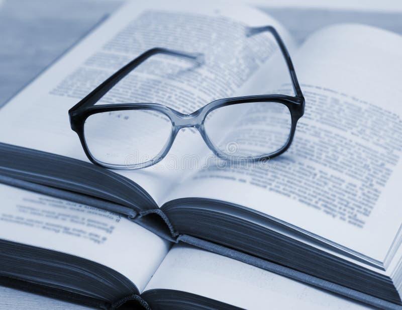 玻璃和开放书在桌上 库存图片