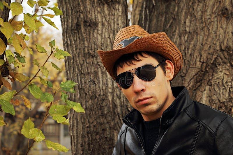 玻璃和牛仔帽的年轻英俊的人 免版税图库摄影