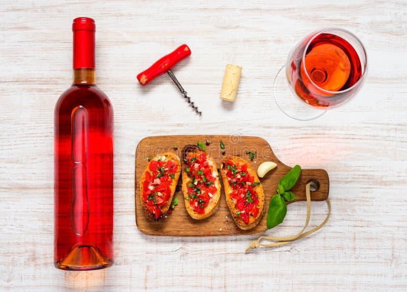 玻璃和瓶与Bruschetta和拔塞螺旋的玫瑰酒红色 图库摄影
