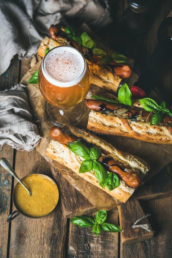 玻璃和瓶未过滤的啤酒,烤香肠狗 图库摄影