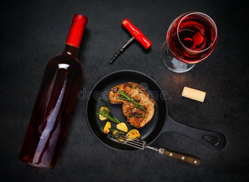 玻璃和瓶玫瑰酒红色用烤牛排 免版税库存图片