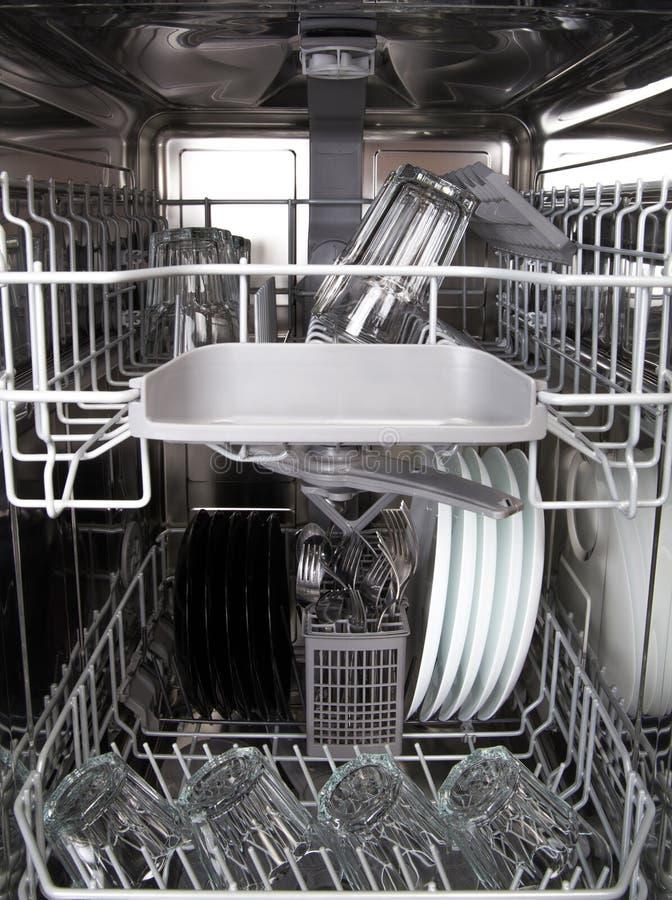 玻璃和白色板材在一个现代洗碗机机器 免版税库存照片