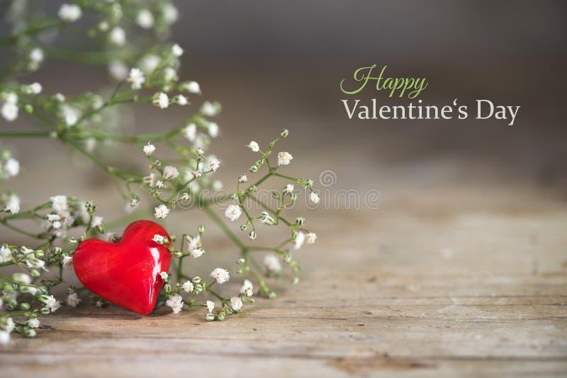 从玻璃和白花的小红色心脏在一土气木 免版税图库摄影