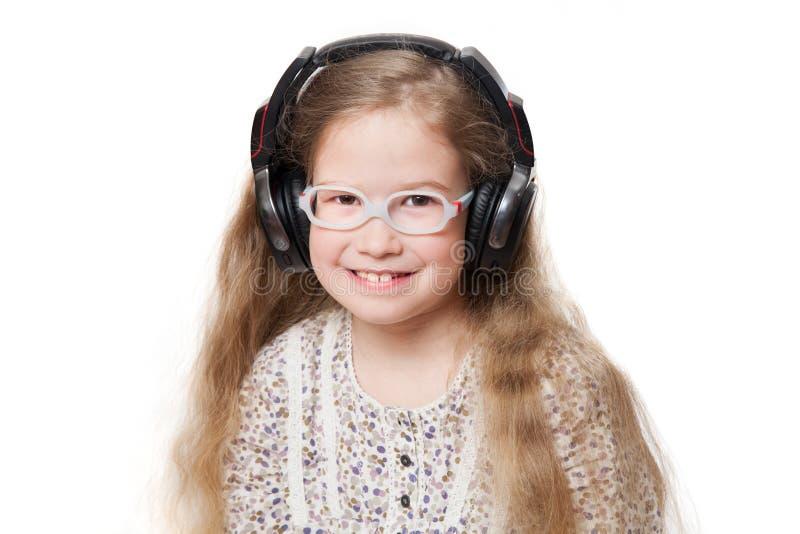 玻璃和耳机的愉快的女孩 免版税库存图片