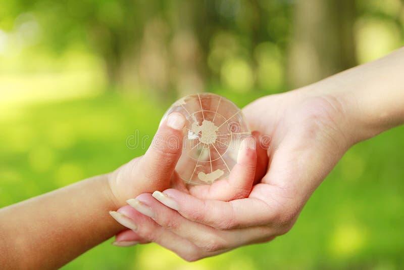 玻璃地球在父母和孩子的手上 免版税库存图片