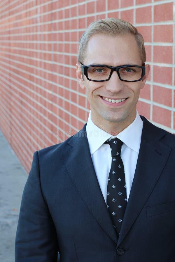 玻璃微笑的白肤金发的年轻聪明的人 免版税图库摄影