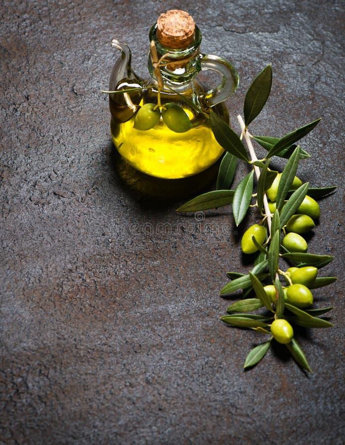玻璃瓶处女橄榄油和分支用橄榄 免版税库存照片
