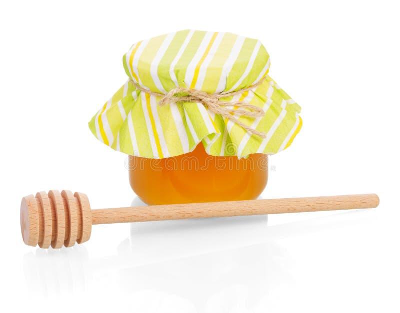 玻璃瓶子用在白色和木浸染工隔绝的蜂蜜 免版税库存照片