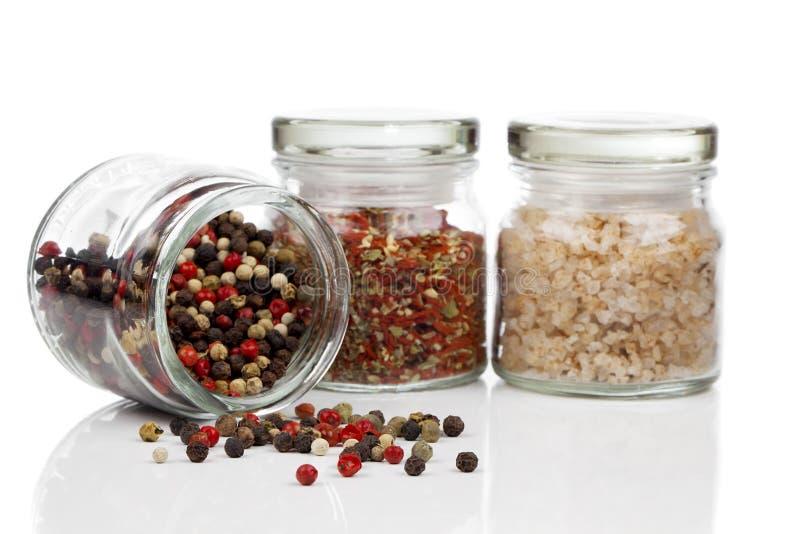 玻璃瓶子用色的胡椒混合,红辣椒和盐 图库摄影