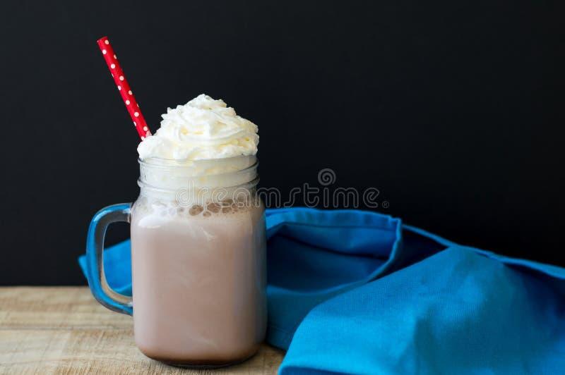 玻璃用与被鞭打的奶油色顶部的热巧克力 库存照片