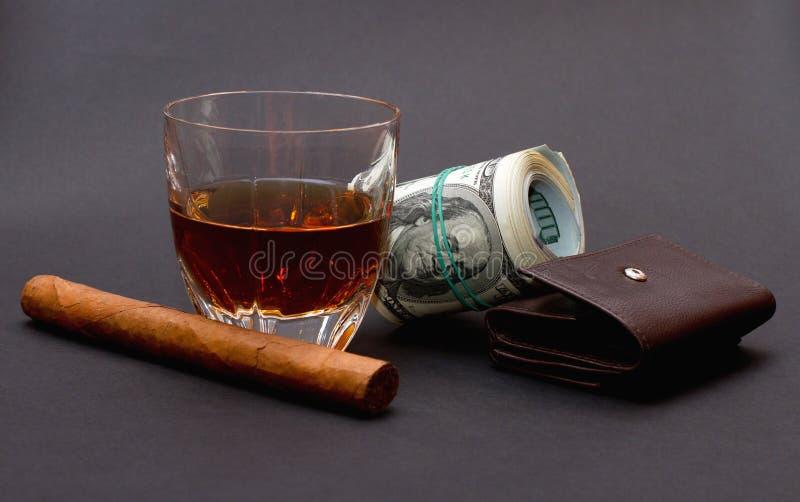 玻璃用威士忌酒、雪茄和金钱卷在一个棕色钱包的在黑暗的背景 免版税库存图片