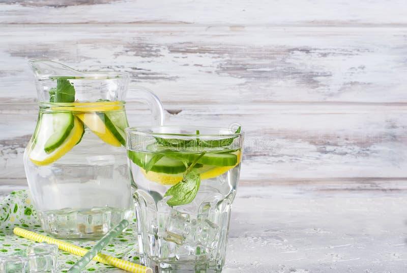 玻璃用戒毒所新鲜的有机黄瓜、柠檬和薄菏浇灌 库存图片