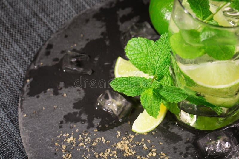 玻璃用酒精饮料填装了从水多的石灰,兰姆酒,新鲜薄荷并且击碎了冰 mojito饮料特写镜头  库存图片